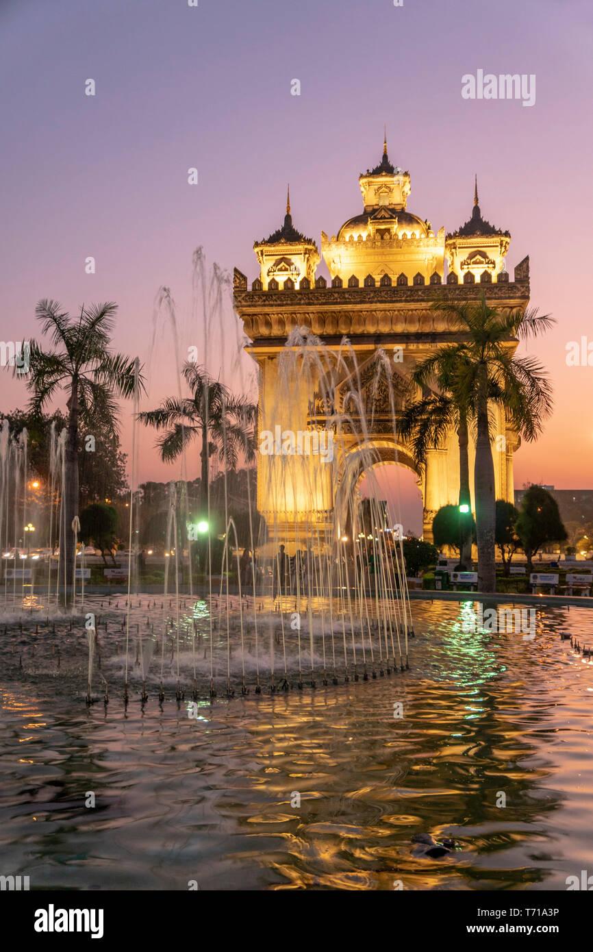 Fountains near Patuxai monument aka Gate of Triumph at night, Vientiane, Laos Stock Photo