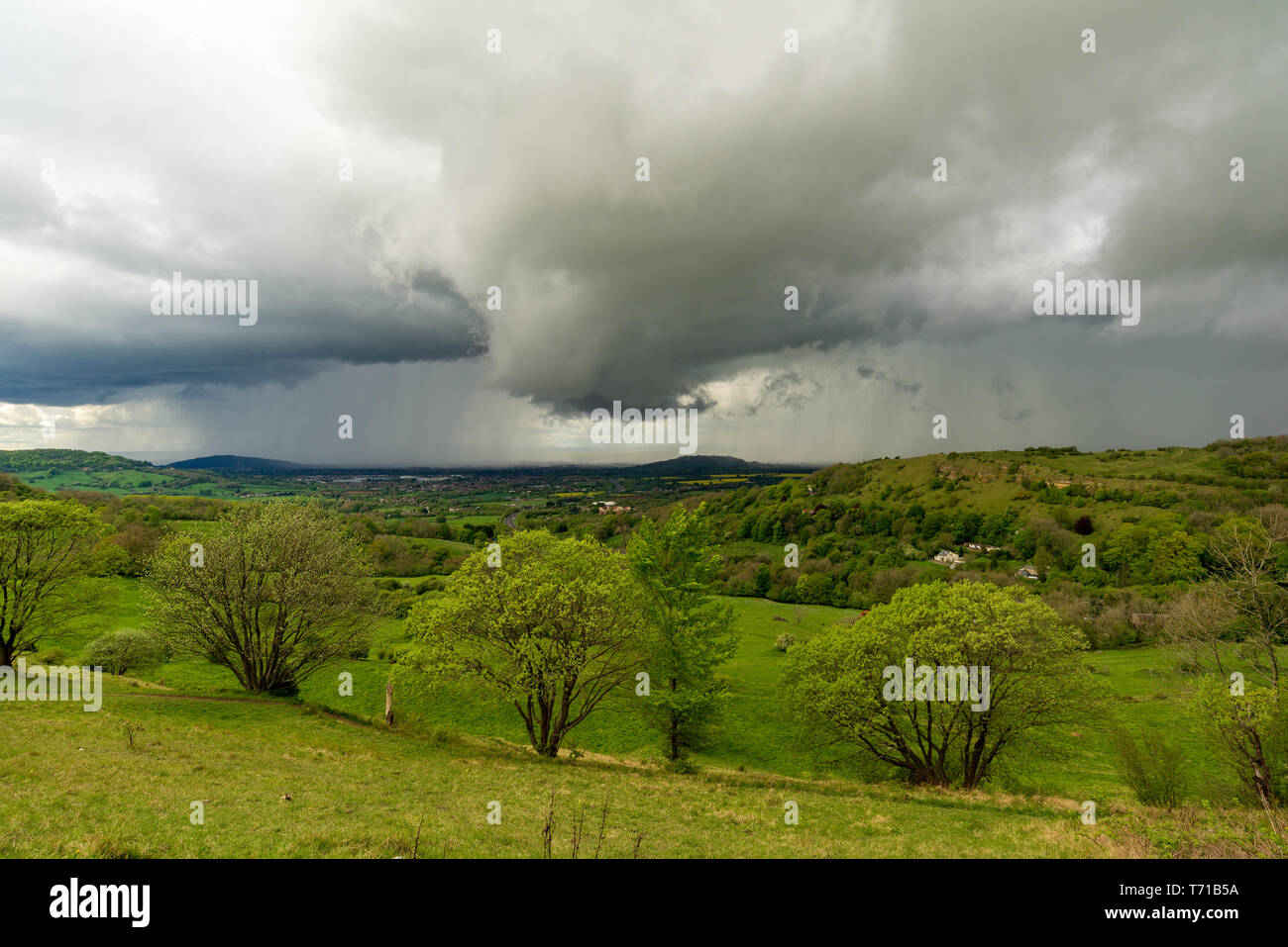 Dark cumulonimbus thunderstorm clouds over Gloucestershire countryside seen from high viewpoint at Birdlip on the edge of the Cotswolds escarpment, UK - Stock Image