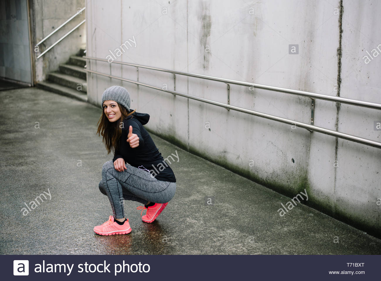 Sporty woman taking a rest during urban outdoor morning fitness and running workout. Female athlete doing thumbs up success gesture. - Stock Image