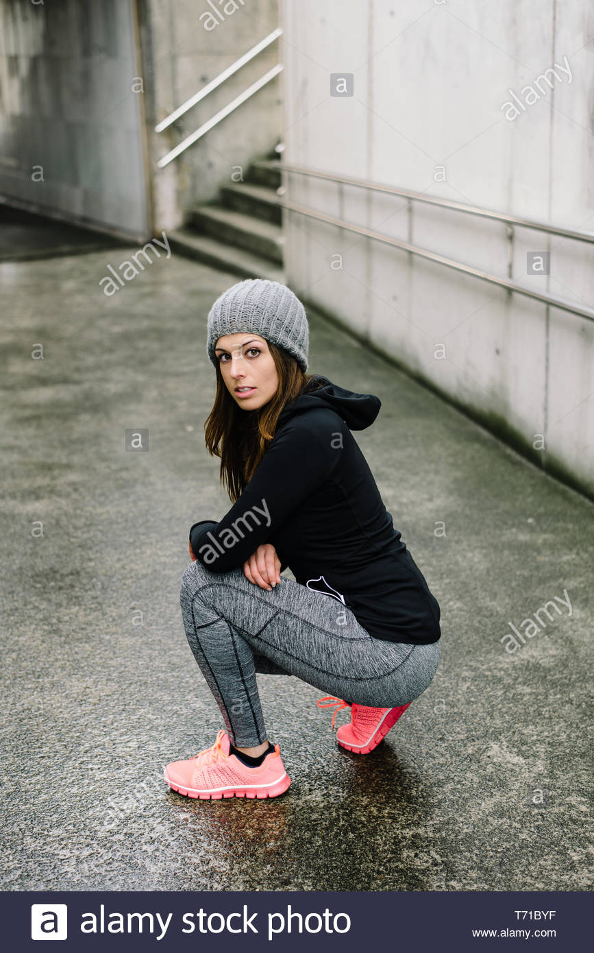 Fit sporty woman taking a rest during urban running and fitness outdoor workout in rainy winter. Stock Photo