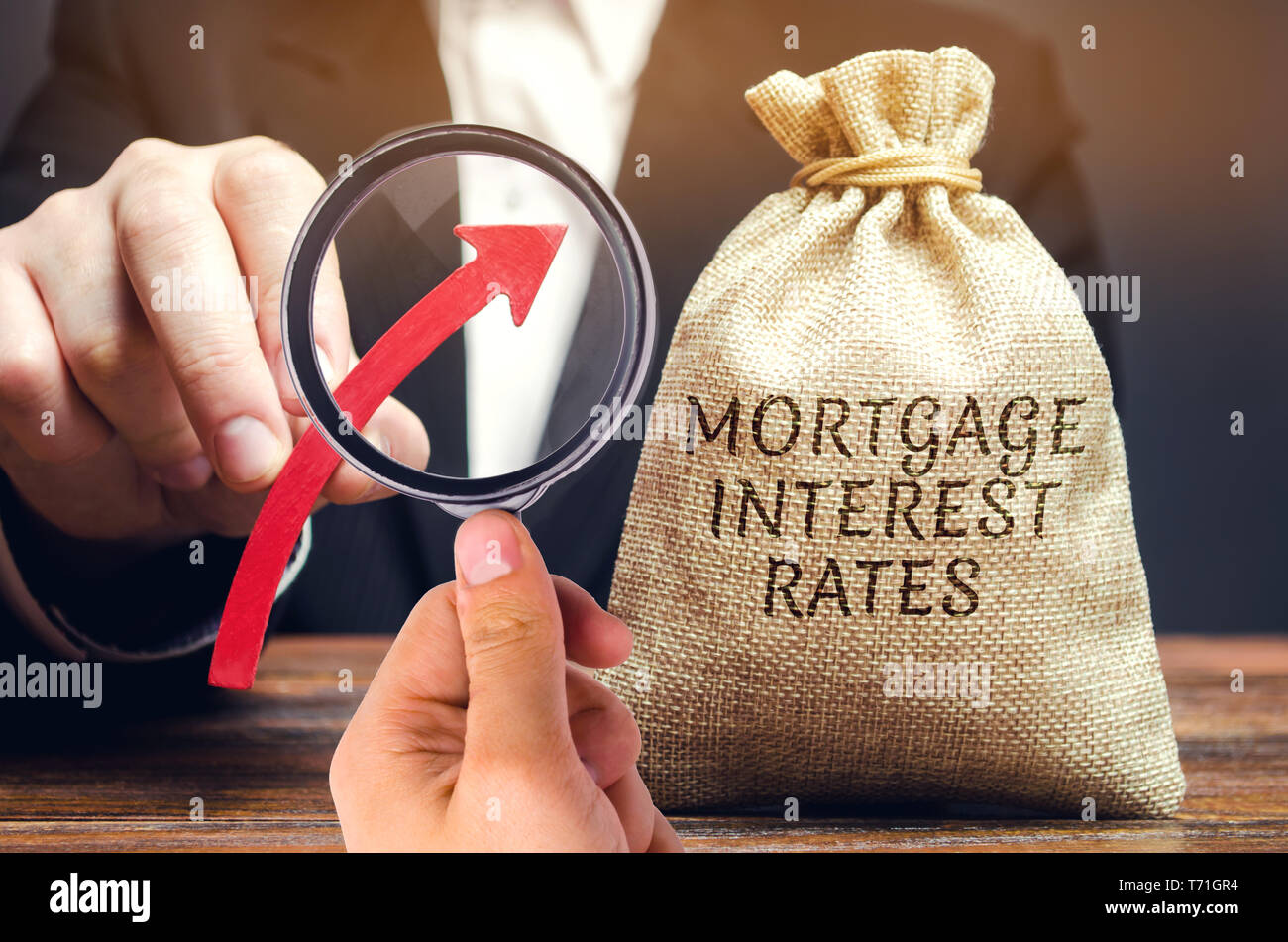 Bag with the money and the word Mortgage interest rates and up arrow in male hands. Raising mortgage rates and tax. The increase in interest charges.  - Stock Image