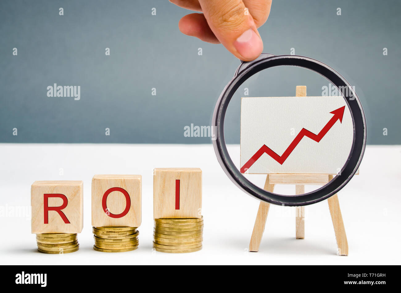 Wooden blocks with the word ROI and a poster with an arrow up. High level of business profitability. Return on investment, invested capital, rate. Suc Stock Photo