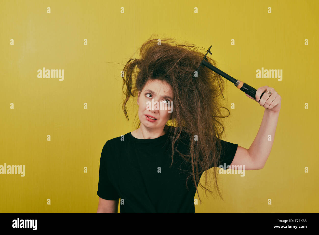 annoyed girl combs her hair  - Stock Image
