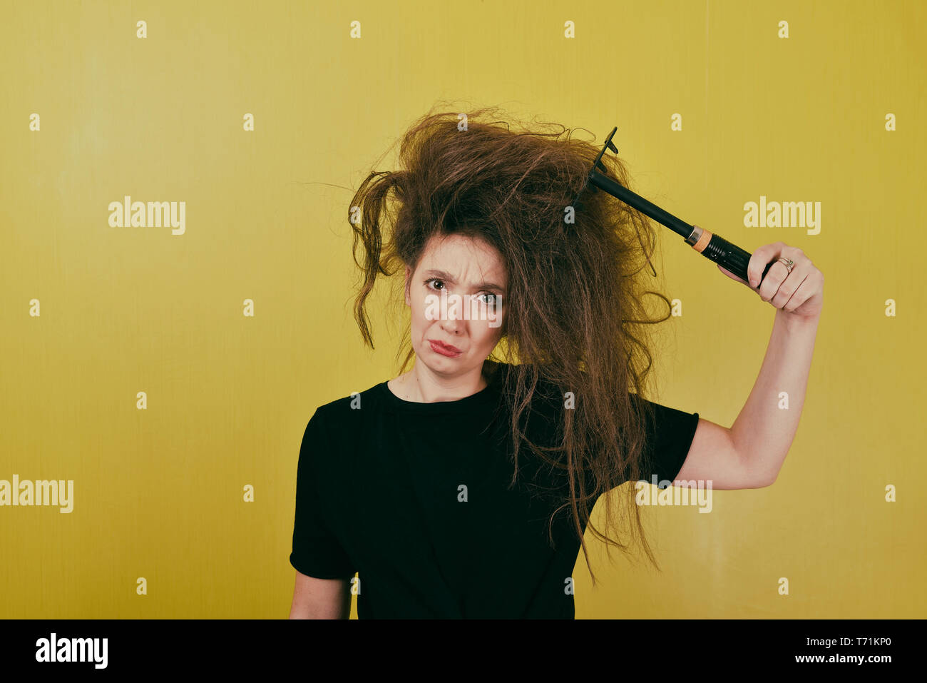 annoyed girl combs her hair  Stock Photo