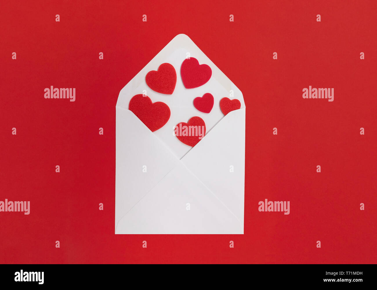 Love letter concept. White envelope with hearts spilling out, with a red background. - Stock Image