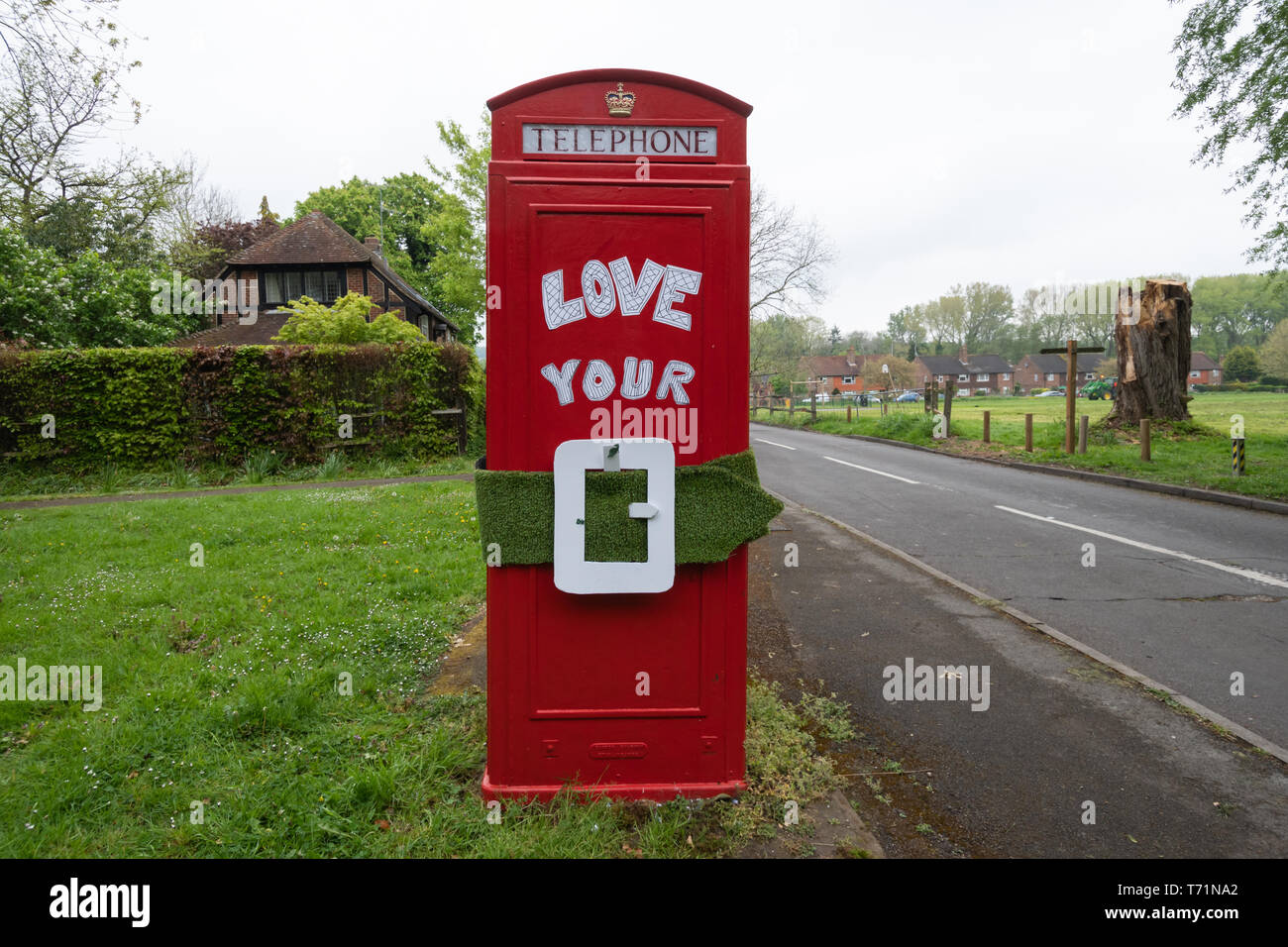 Red telephone box (phone box) with the message Love your Green Belt, a protest about local policy threatening the green belt near Guildford UK - Stock Image