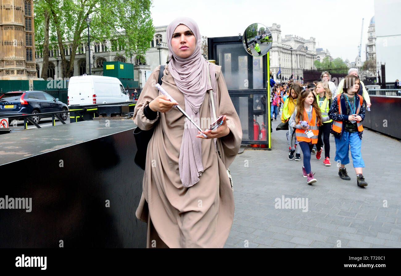 London, England, UK. Woman in Islamic dress with her mobile phone by the Houses of Parliament - Stock Image