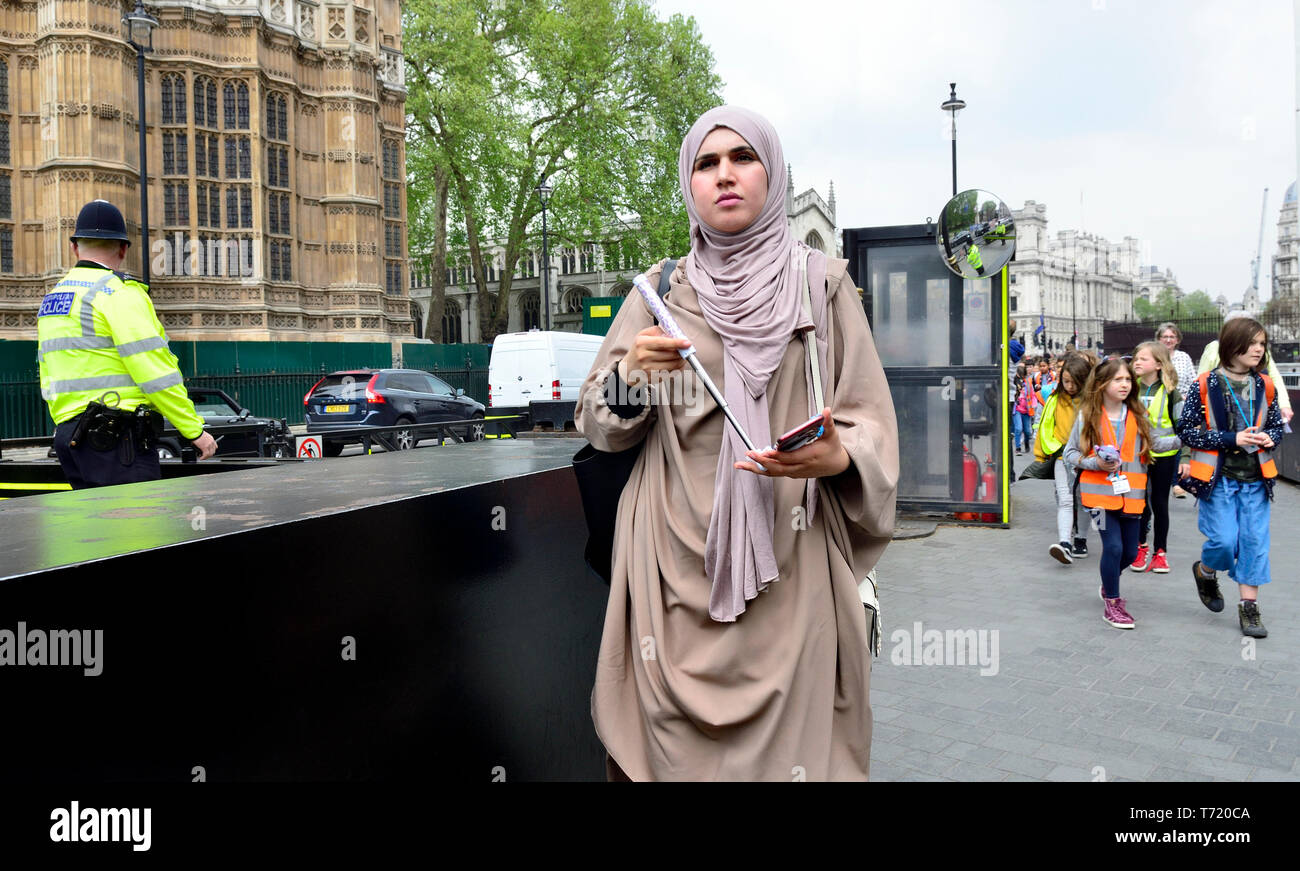 London, England, UK. Woman in Islamic dress with her mobile phone by Westminster Abbey - Stock Image