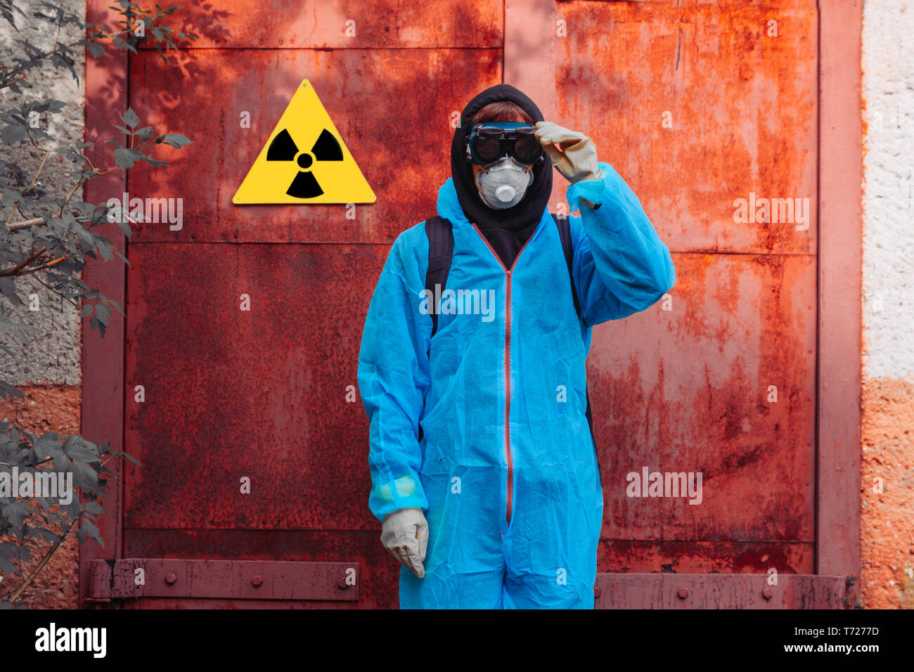 Men in blue protective overall near icon of radiation poisoning. Concept of environmental polution and ecological catastrophe. - Stock Image