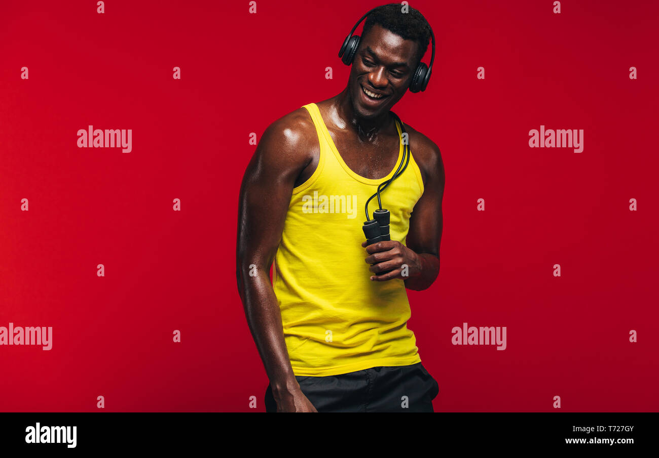 Fit young man listening to music on headphones with a skipping rope in hand on red background. Fit young man taking after from workout. - Stock Image