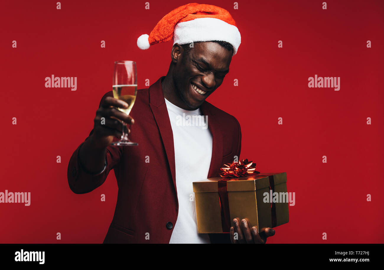 573ba2a4976b7 African man wearing santa hat with champagne and gift box against red  background. Happy young