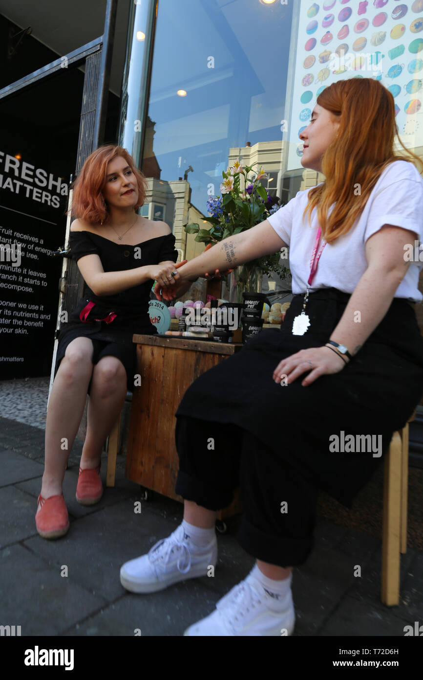 A woman receives a hand massage on the street from a masseuse. - Stock Image