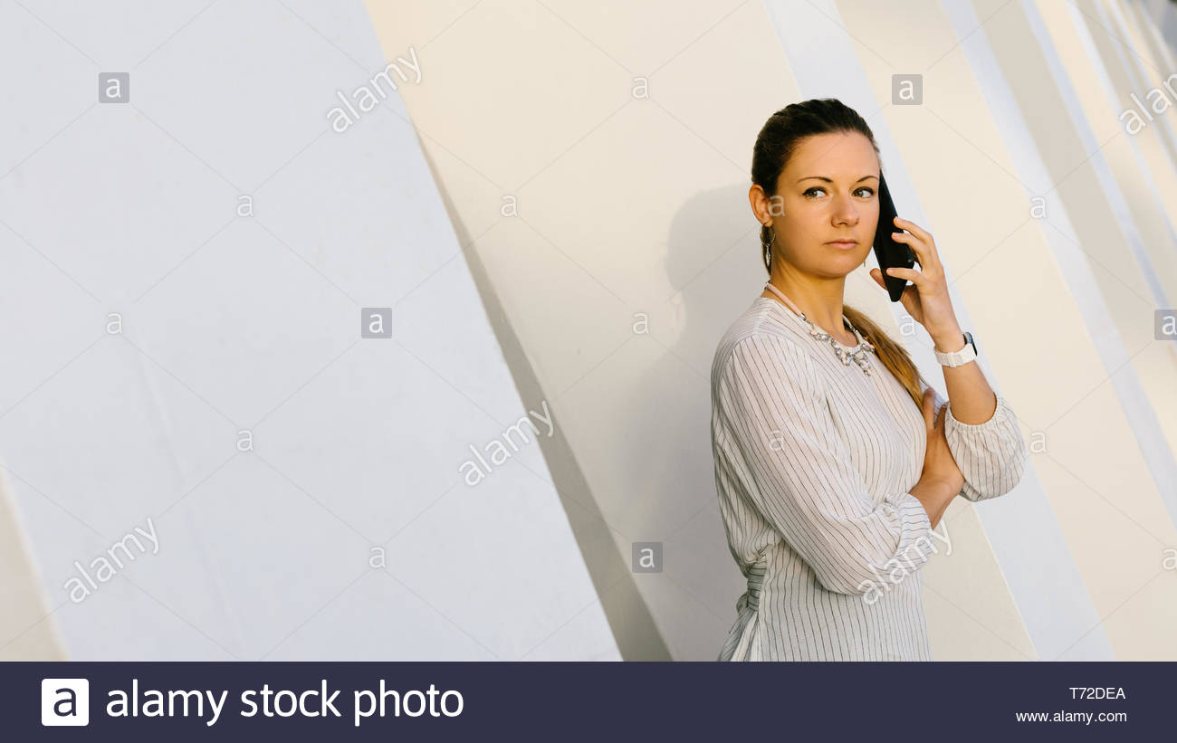 Confident young professional woman on cellphone business call outside modern corporate building. Stock Photo