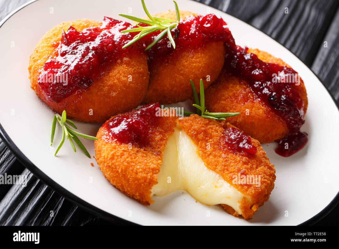 Fried Camembert breaded filed with cranberry sauce and rosemary close up on a plate on the table. horizontal - Stock Image