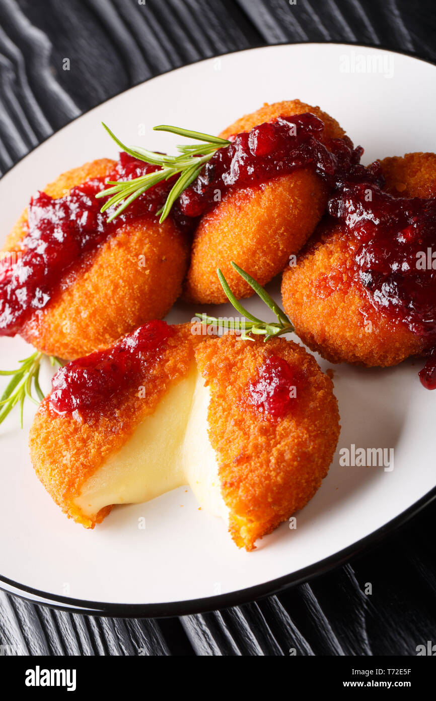 Delicious Baked Camembert Cheese Breaded with Cranberry Sauce and Rosemary closeup on a plate on the table. vertical - Stock Image