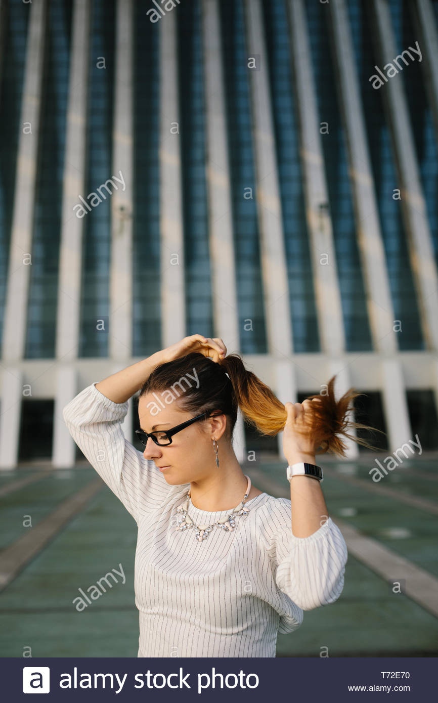 Young professional woman lacing ponytail outside corporate building. Female business style. - Stock Image