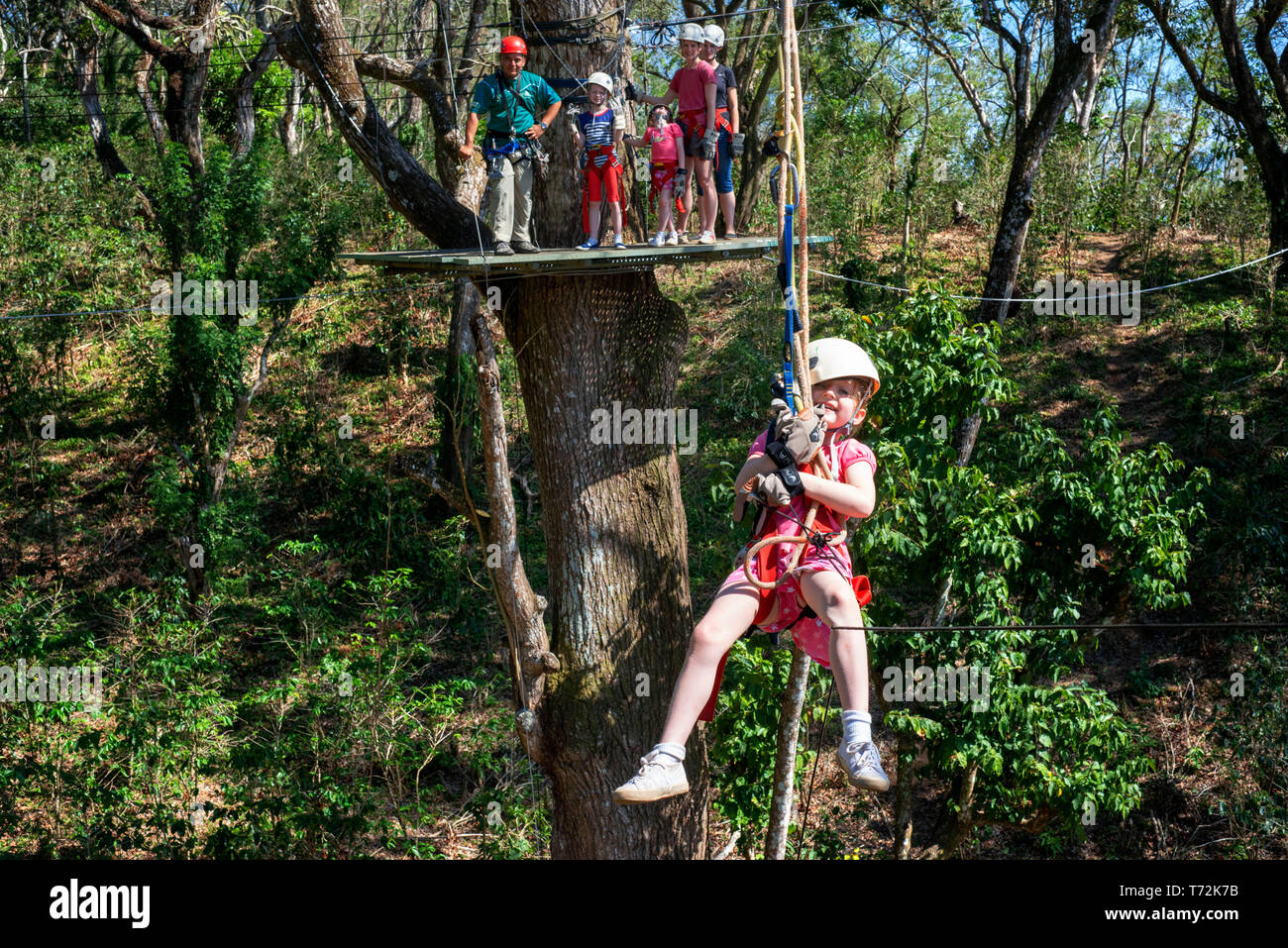Young girl in a Canopy Adventure Café Las Flores Nicaragua Central America. Zip line across the treetops using the most advanced high angle equipment  - Stock Image