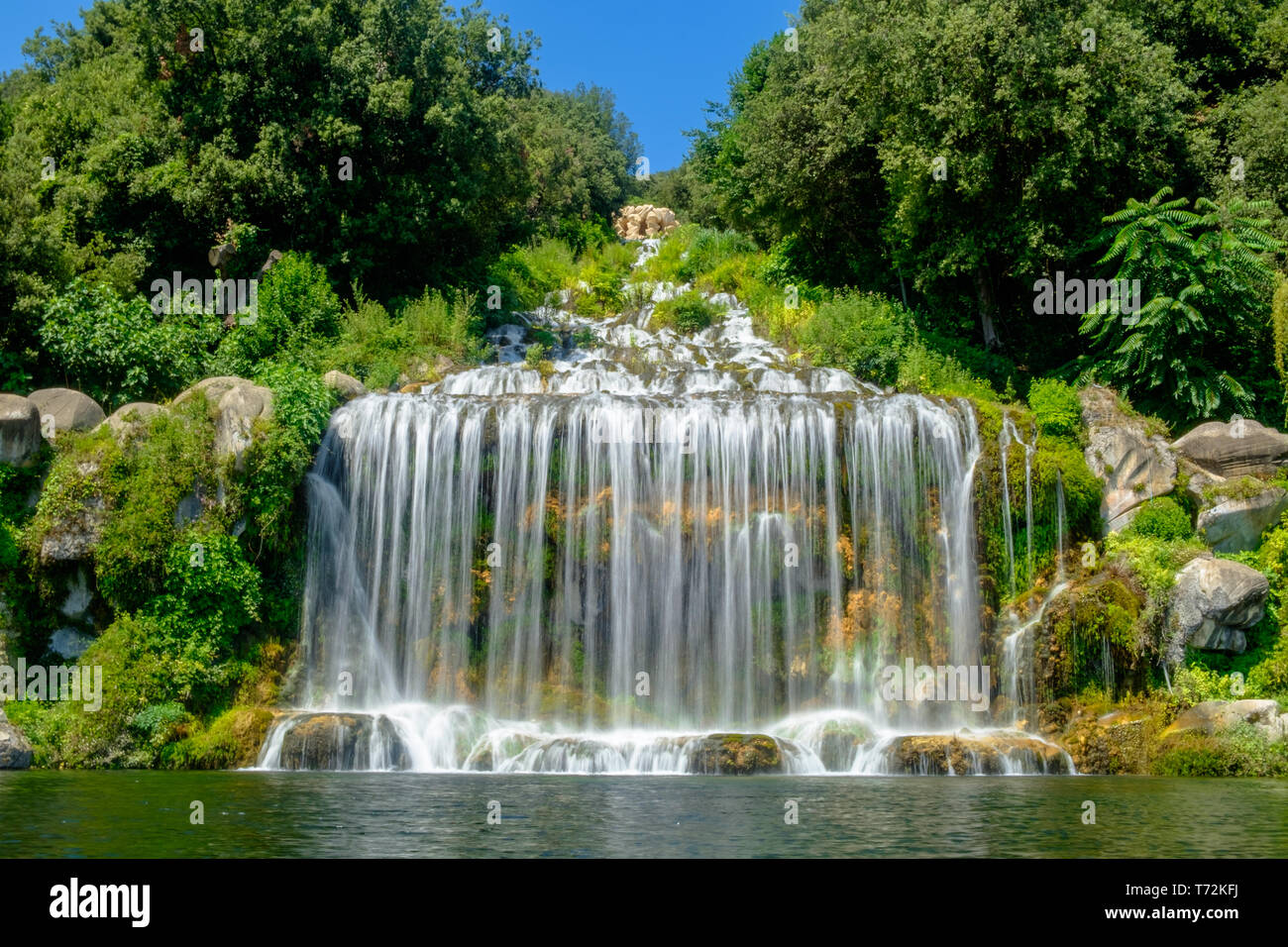 The big waterfall at the end of the park of the 'Reggia di Caserta' falls as a water curtain. The water streams down Briano mountain. - Stock Image