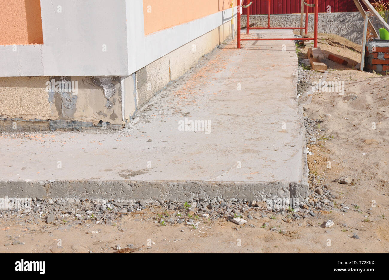 Close up on house foundation waterproofing, damp proofing with concrete path to avoid water leaks for house wall. - Stock Image
