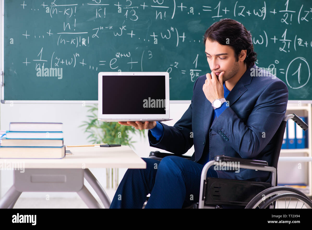 Young handsome man in wheelchair in front of chalkboard Stock Photo