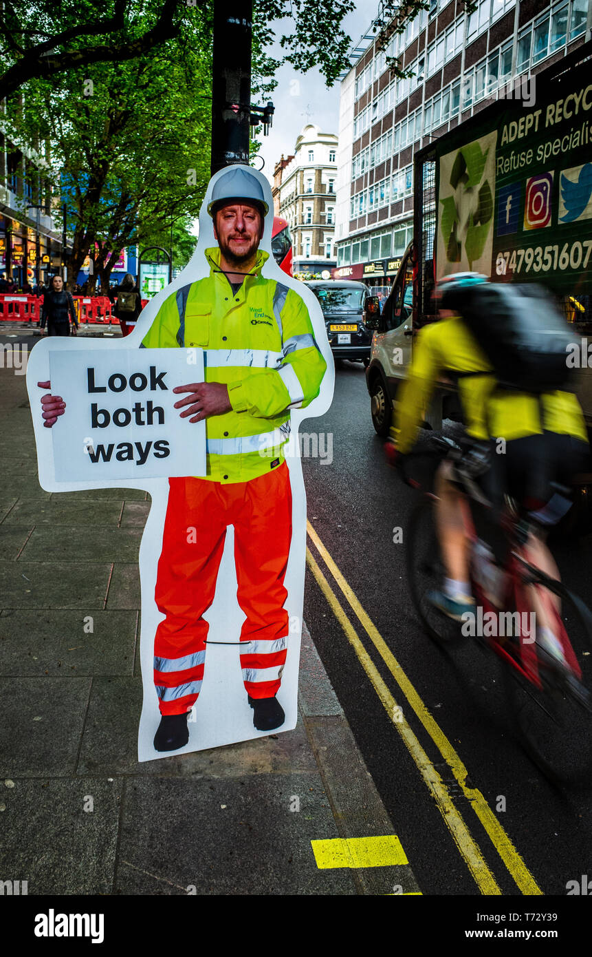 Road Safety Sign - unusual sign telling pedestrians to look both ways in London's Tottenham Court Road as it changes from one way to two way traffic. - Stock Image