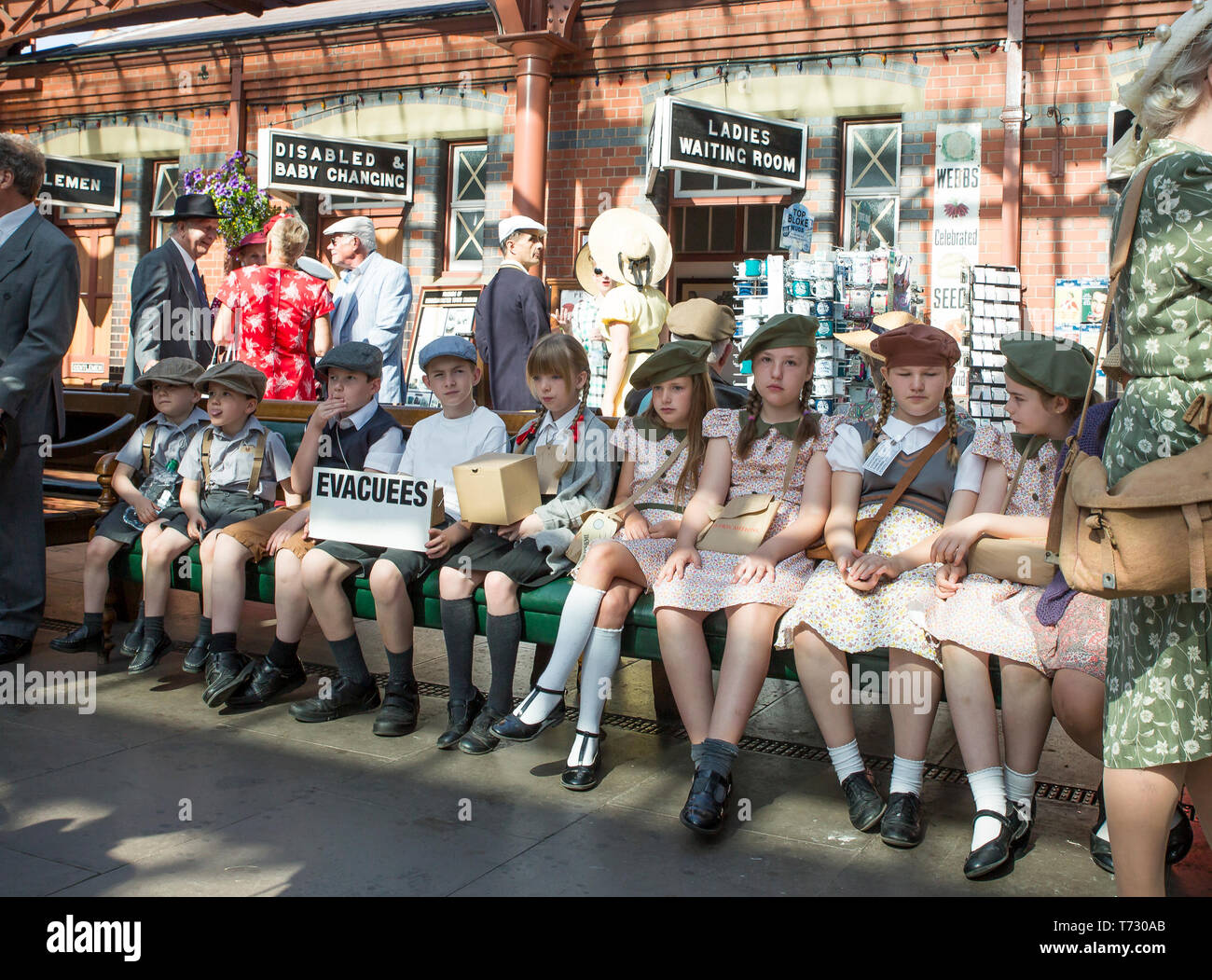 Severn Valley Railway, 1940's wartime event, Kidderminster vintage railway station. Boys & girls (evacuees) in 1940's dress sitting on bench waiting. - Stock Image