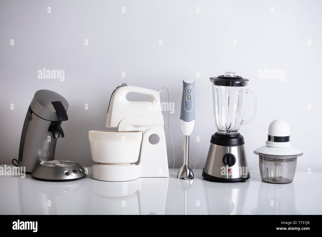 Variety Of Kitchen Appliances In Row Over Reflective Desk