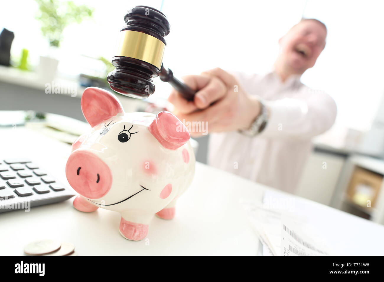 Crazy man with mallet trying to break funny piggybank - Stock Image
