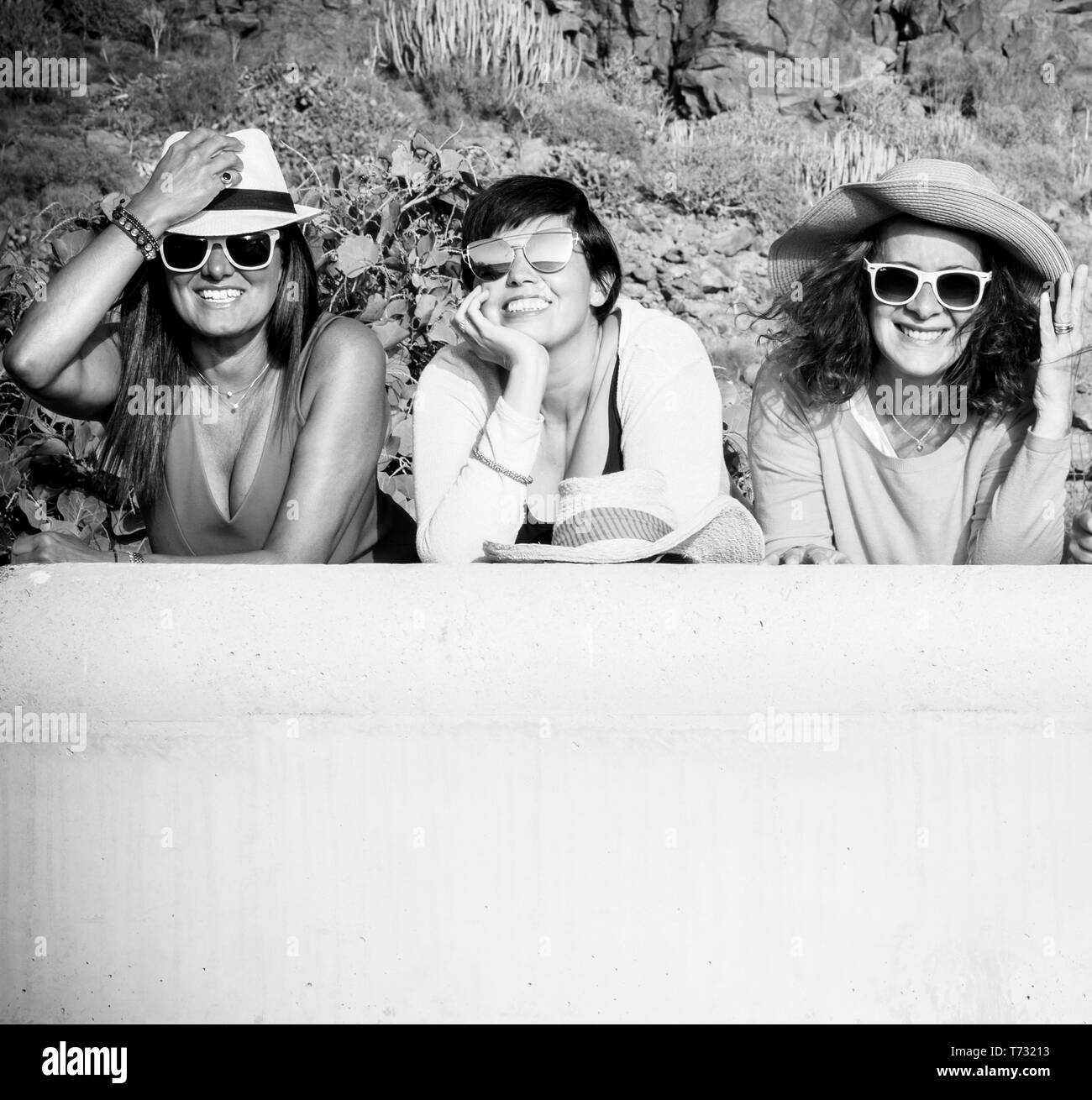 Black and white picture with three cheerful happy caucasian people young women smiling and looking at the camera in outdoor friendship activity - Stock Image
