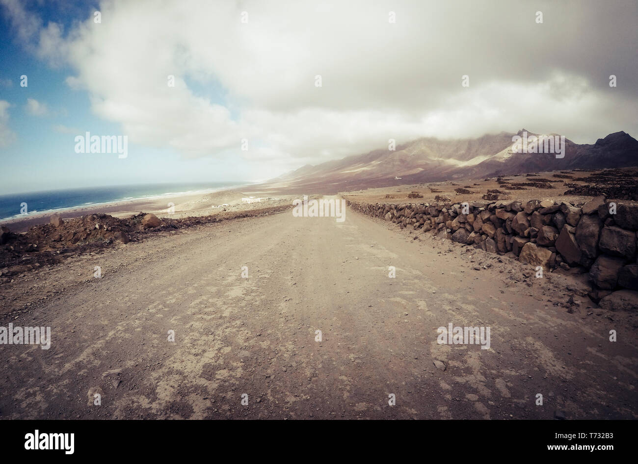 Long off road terrain way road viewed from ground level with mountains and coastline ocean view - travel and adventure concept for alternative vacatio Stock Photo