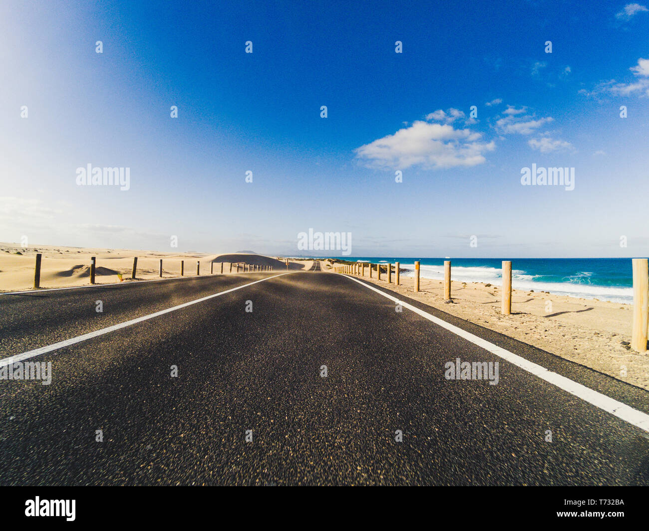 Long way road for travel car transportation concept with desert and beach on the side - sea water and blue clear beautiful sky in background - motion  Stock Photo