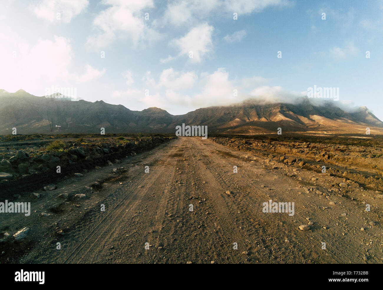 Long off road terrain way road viewed from ground level with mountains and blue cloudy sky - travel and adventure concept for alternative vacation and Stock Photo