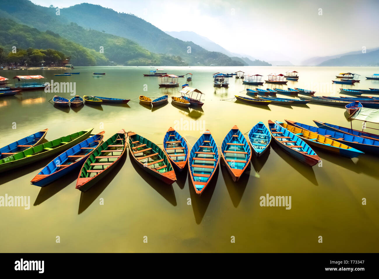 Amazing view on Phewa Lake. colorful boats queued at a midday.Province of Pokhara Nepal - Stock Image