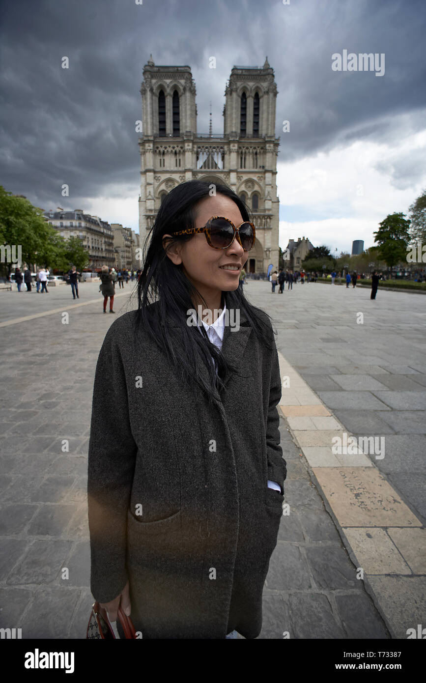 Asian woman posing in front of the Notre Dame cathedral in Paris with dark clouds overhead - Stock Image