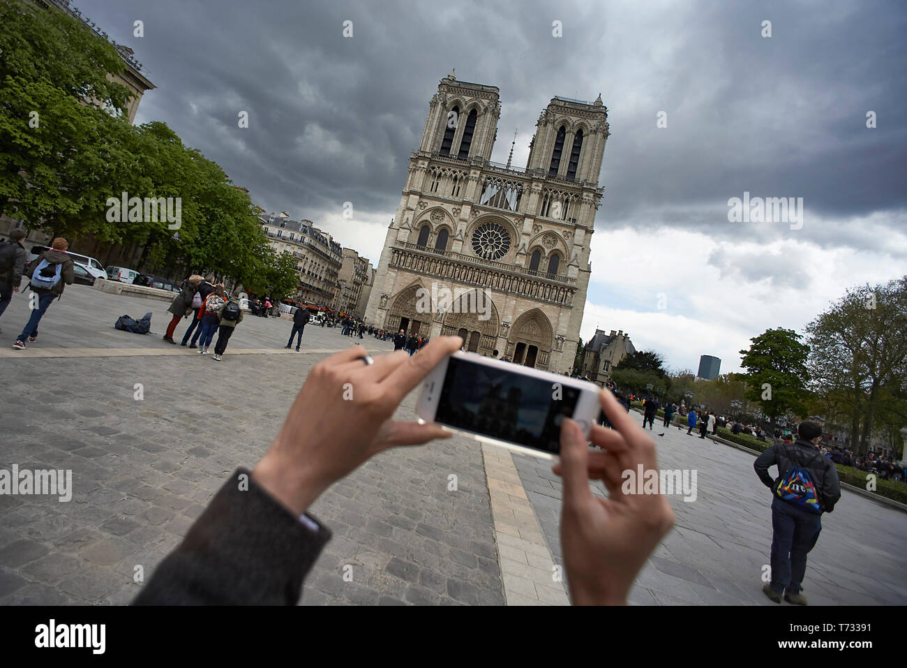POV image of a woman taking pictures using her mobile phone of the Notre Dame cathedral in Paris with dark clouds overhead - Stock Image