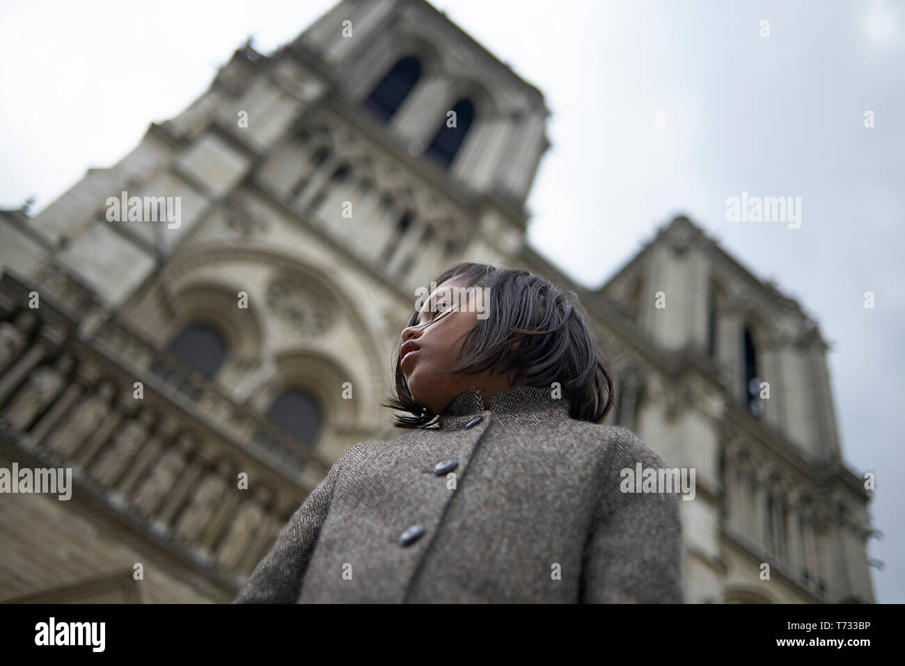 Portrait of a cute young Asian girl posing in front of the Notre Dame cathedral in Paris with dark clouds overhead - Stock Image