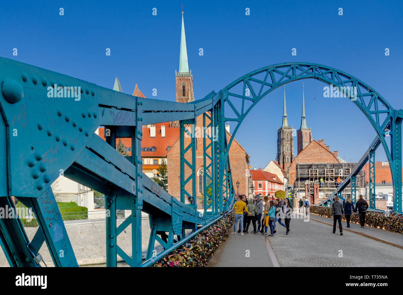 Wroclaw, Lower Silesian province, Poland. Tumski Bridge, leading to the Ostrow Tumski district. Belfries of the Collegiate Church of Holy Cross. Stock Photo