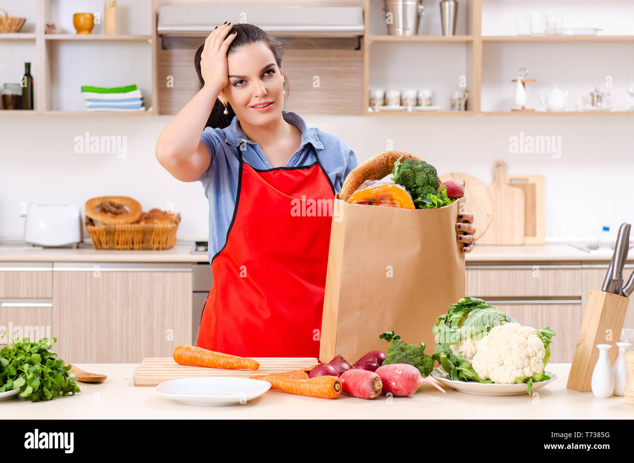 Young woman with vegetables in the kitchen - Stock Image