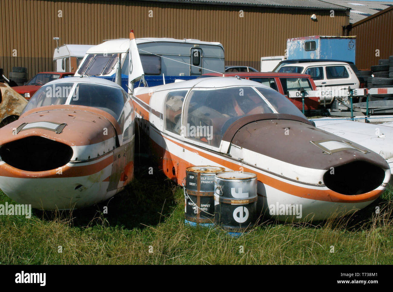 A storage or dumping area at Turweston Aerodrome, Buckinghamshire, UK with two Robin HR100 planes, elf oil drums, cars and caravans. Decaying - Stock Image