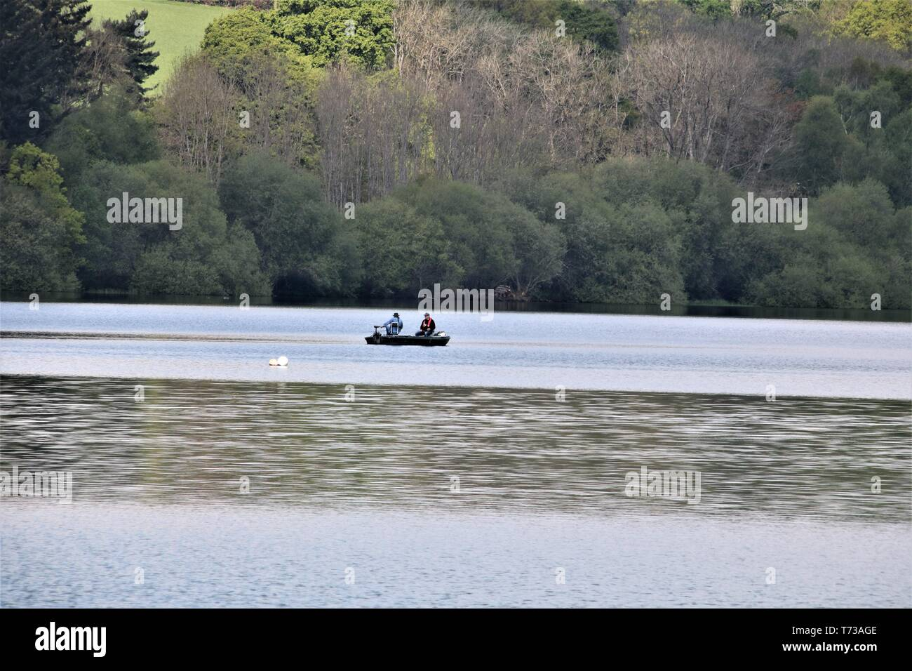 anglers fishing from a boat on ardingly reservoir, sussex, on a nice day - Stock Image