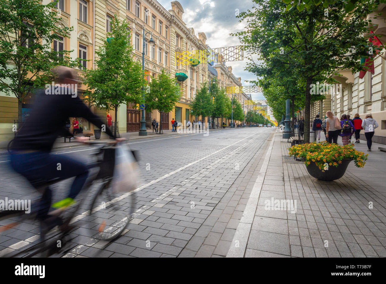 Pedestrian walking down and cyclist swiftly passing by on the main commercial street of Vilnius, Lithuania - Stock Image