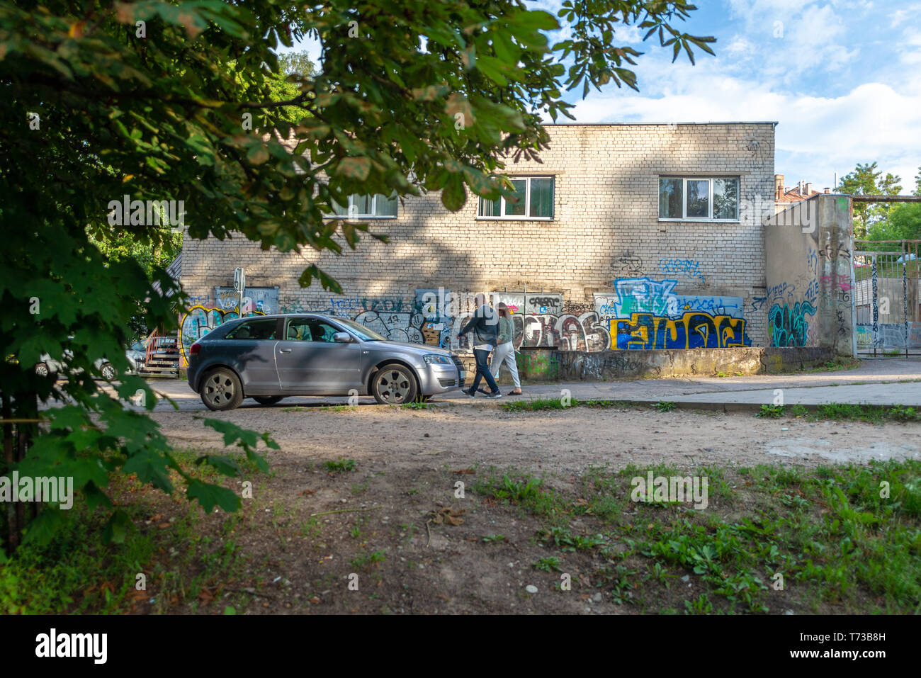 A couple is walking in front of graffiti on a back alley in Vilnius, Lithuania Stock Photo