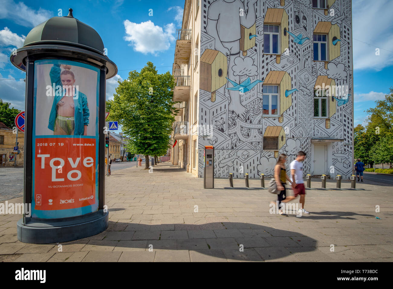 VILNIUS, LITHUANIA - JULY 7, 2018: Two passersby and and advertising (Morris) column in the historical center of Vilnius Stock Photo