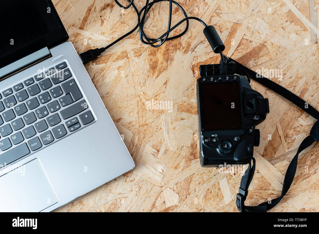 notebook connected to a digital SLR camera with usb cable, thetering mode, on a desktop - Stock Image