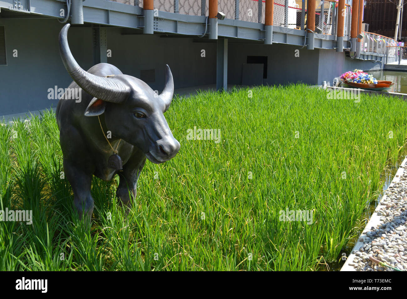 Milan/Italy - June 30, 2015: View to a green rice camp with sculpture of big horns ox standing on it at the Thailand pavilion of the EXPO Milano 2015. - Stock Image