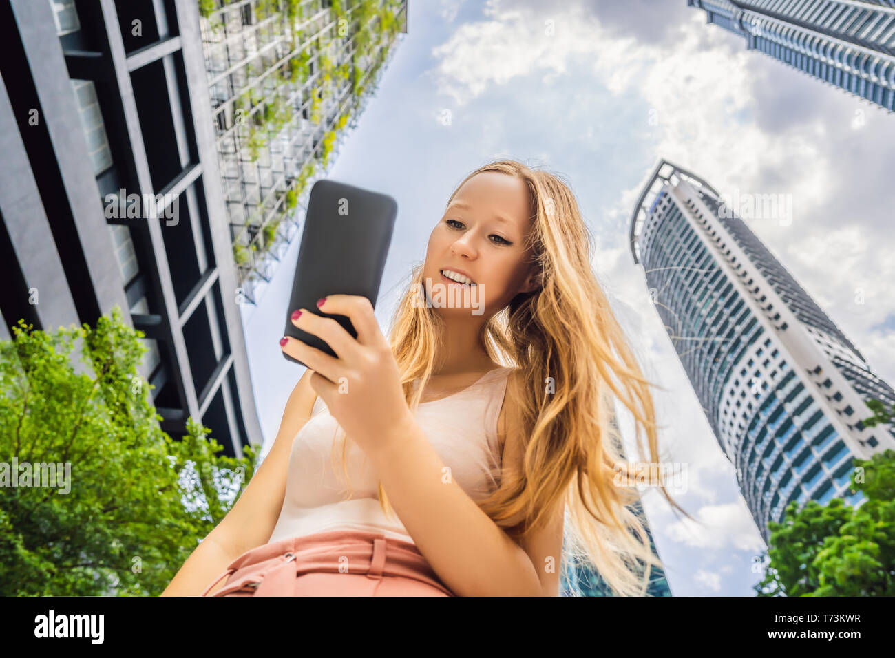 woman using map app on smartphone on the background of skyscrapers - Stock Image