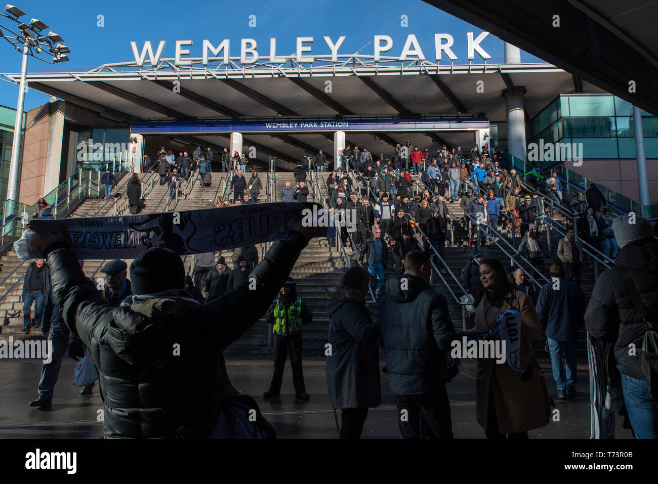 Scarves sellers wait outside Wembley Park station for the thousands of football supporters at Wembley Park for a Premier League game between Tottenham - Stock Image