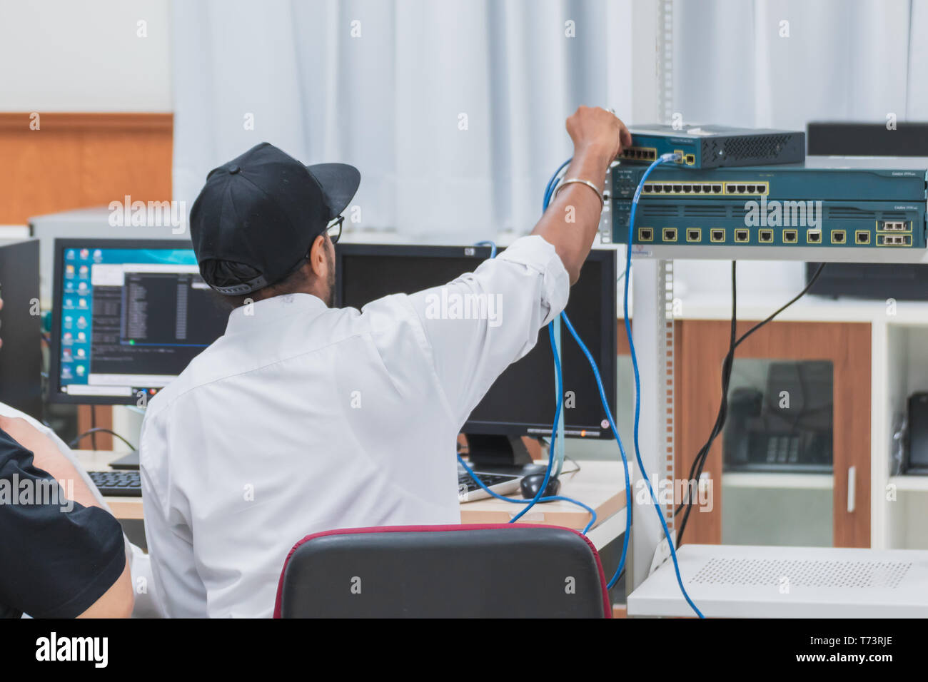 Back of Asian University students majoring in Computer Engineering working on their computer networking project. One student configuring a network swi - Stock Image