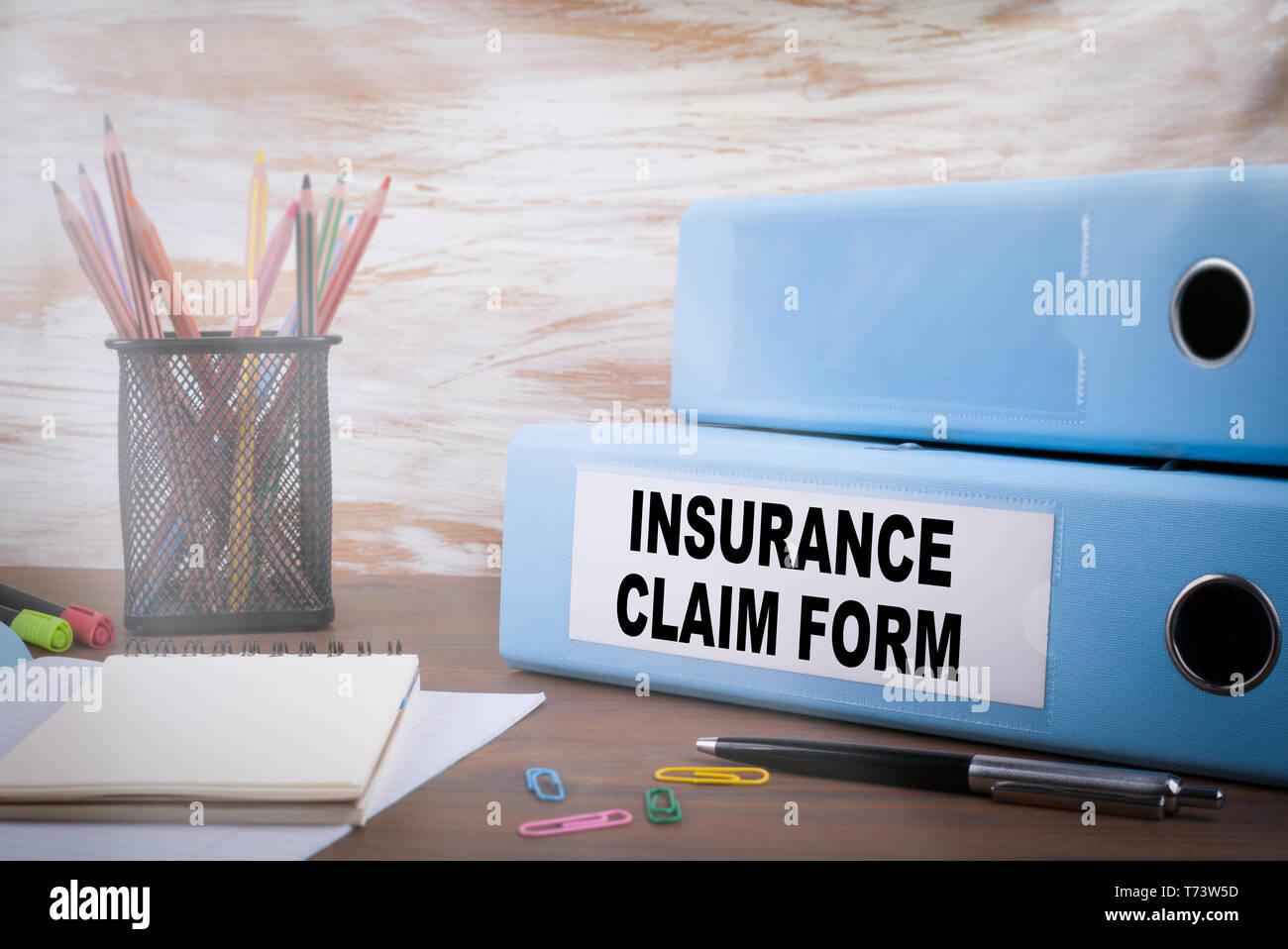 Insurance Claim Form, Office Binder on Wooden Desk - Stock Image