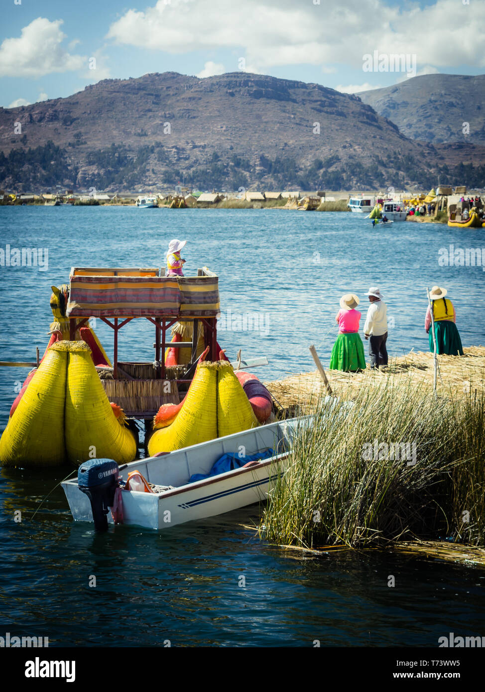The Uros floating islands in lake Titicaca, Peru. Typical boat and natives - Stock Image